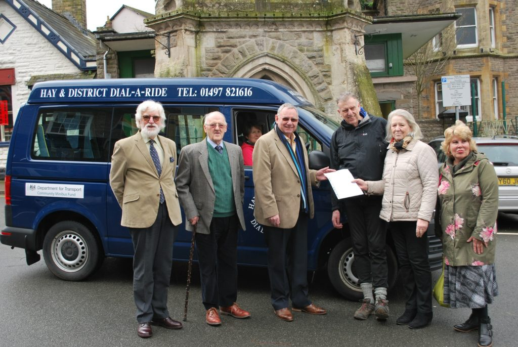 From left: W Bros Nigel Boothby and Peter Like, of Loyal Hay Lodge; volunteer driver Kate Haines; RW Bro Michael Holland, Provincial Grand Master; David Morris, volunteer driver; Mary Fellowes, Chair of the charity; and Gillian Jones, director of the charity, in front of one of the minibuses by the clock tower in Hay on Wye